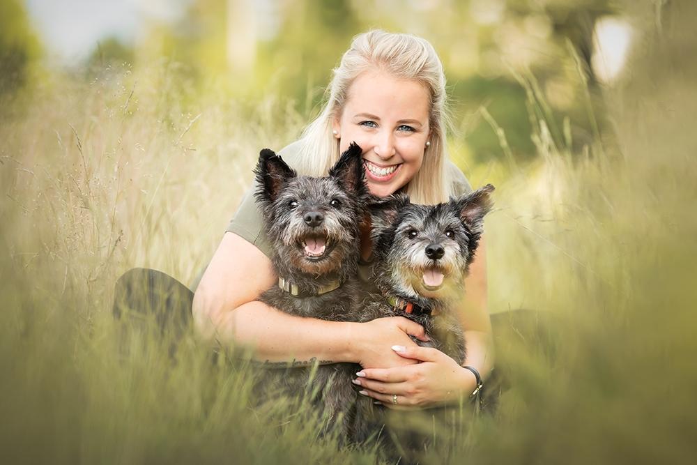 Besitzerin sitzt im Gras und umarmt Hunde