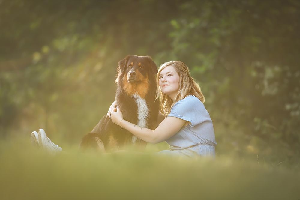 Mensch mit Hund sitzen im Gras