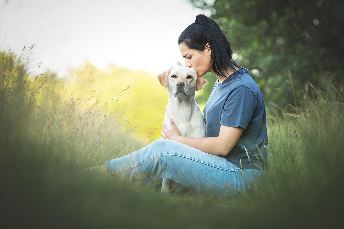Besitzerin umarmt Labrador im Gras